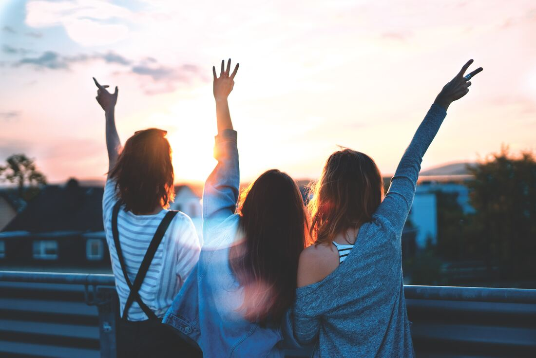 3 friends facing the sunset with their hands in the air