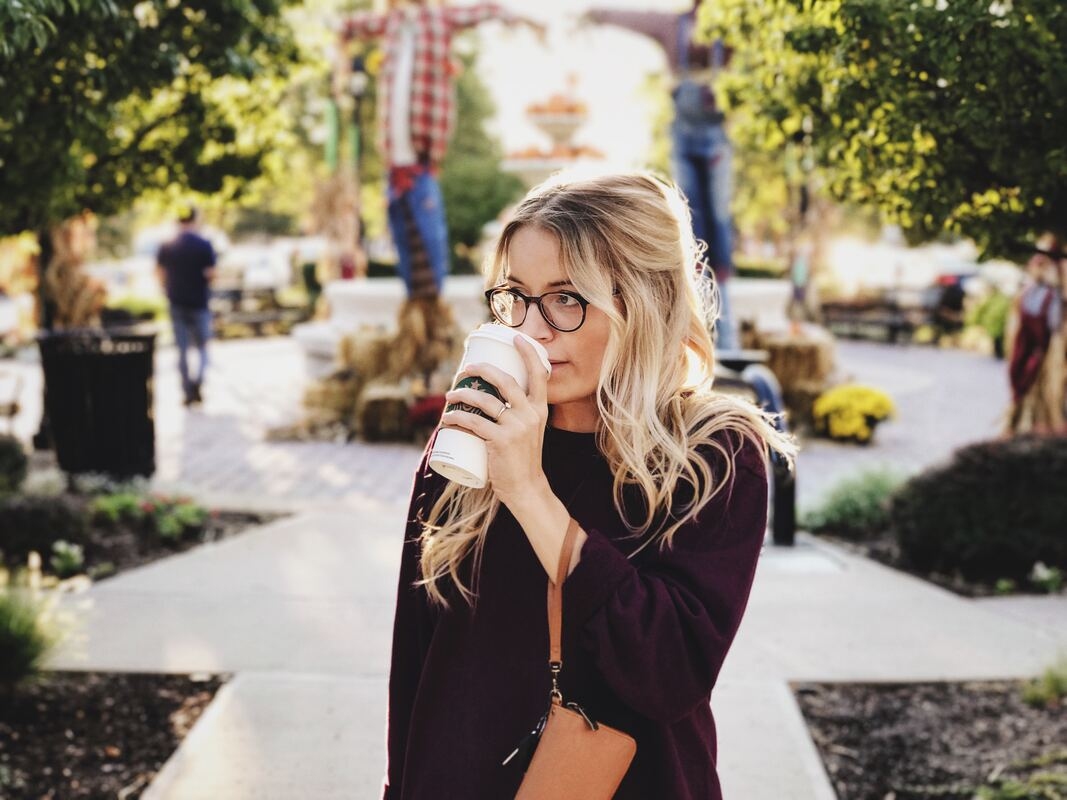 blonde female entrepreneur drinking Starbucks in the park