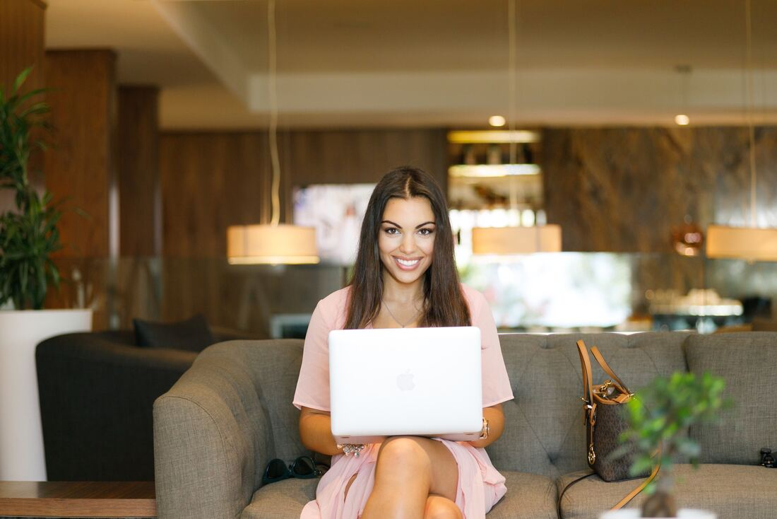 female business owner sitting on couch with laptop