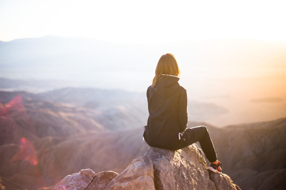 female entrepreneur sitting on mountain top at sunset