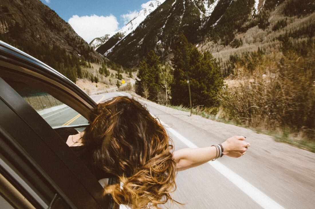 girl hanging out the window on a road trip through mountains