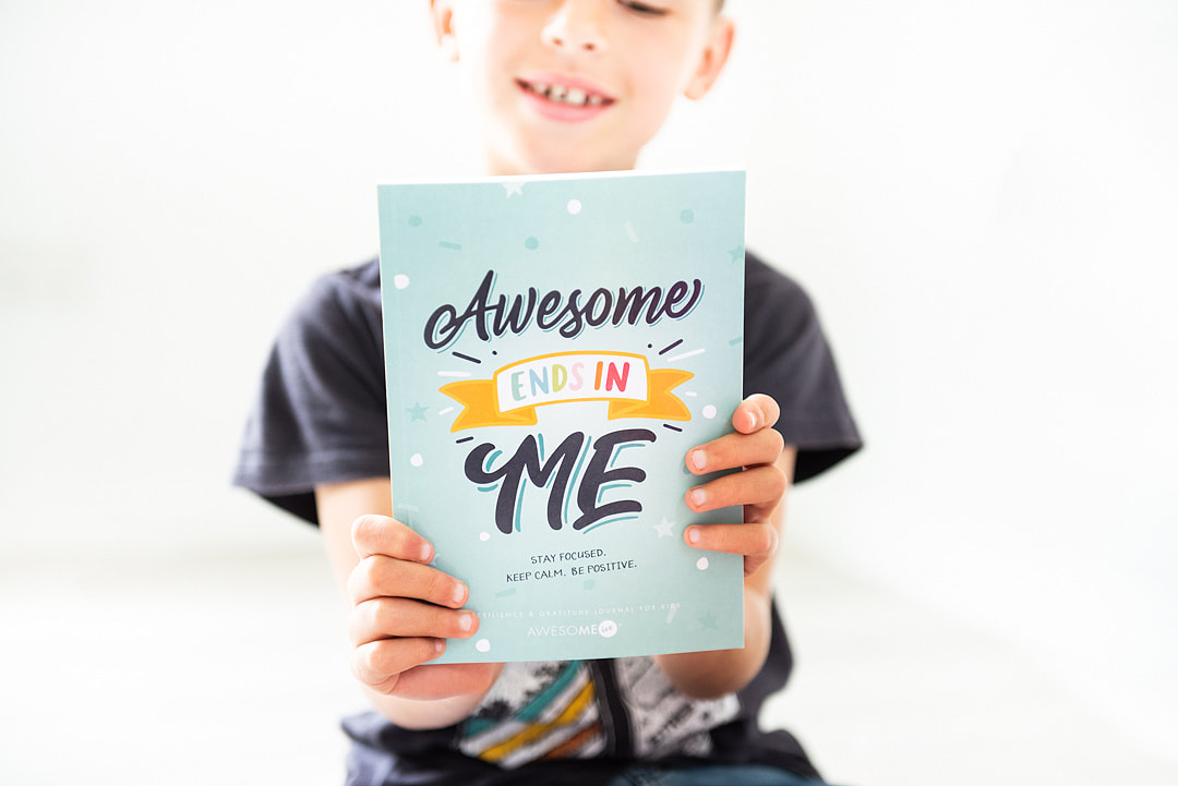 kid holding up AwesoME Inc resilience journal