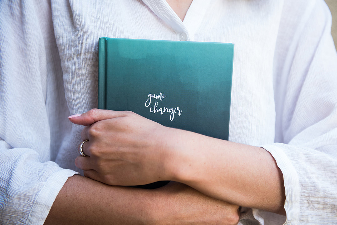 woman holding green resilience journal to her chest