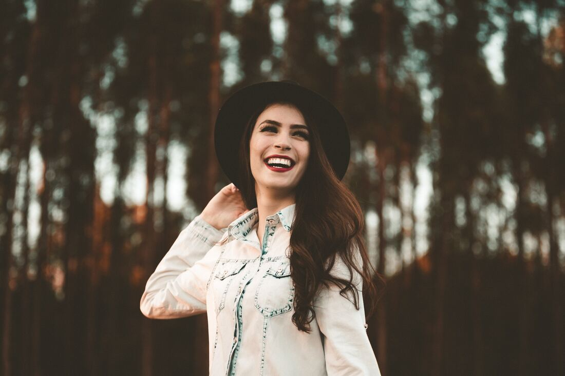 woman in black hat and denim shirt smiling in the forest